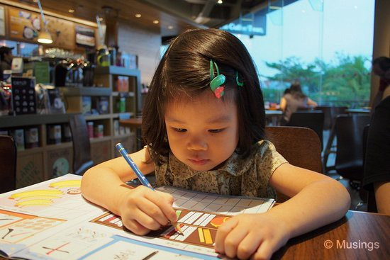 Practising her Chinese character strokes while waiting for our breakfasts to be served. She plows through those workbooks.