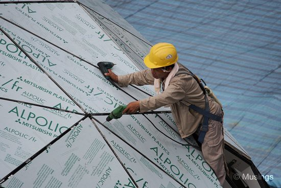 A worker aligning the plastic sheets covering the badminton dome.