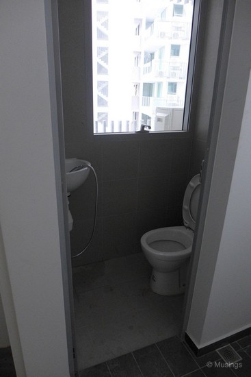The toilet adjacent to the kitchen.