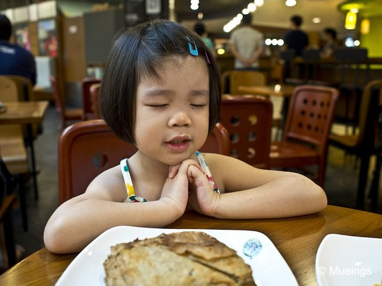 "Saying Grace for her mushroom-pie thingie at Starbucks @ Hougang Mall. She still ends her prayers with ""Thank you God for Daddy, Mommy, Peter, and Hannah!"""