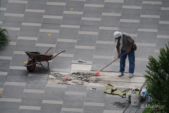 This was odd - a worker cleaning up debris near the Main Pool. It looked like the tiles had been removed, and now need replacements.