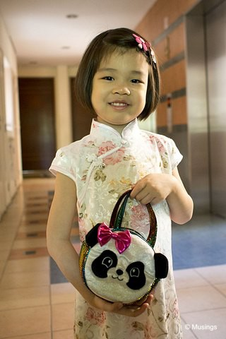 "Hannah in her Cheongsam on the first day of CNY. She's carrying a little Panda bag (""To hold all my ang pows!"") that a visiting friend from the US brought along last year."