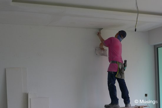 A worker who is wearing a reverse-cap means business! The ceiling boards' surfaces are not perfectly smooth, so they are layered over to get them ready for painting.
