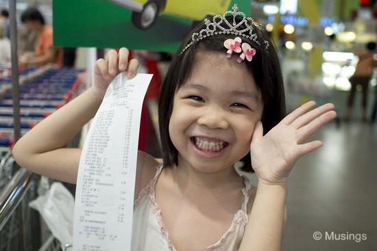 Not sure what she's thrilled about, but that's the Fairprice Supermarket cash receipt for our groceries.