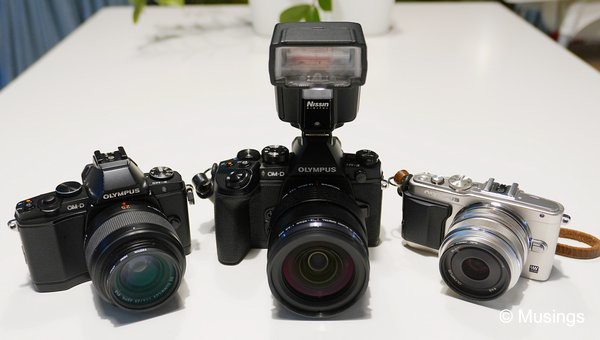 Three of the four m4/3 cameras I've got now in possession; the 3.5 year old E-M5, the E-M1 with the 12-40mm and the Nissin i40 flashgun, and the E-PL6.